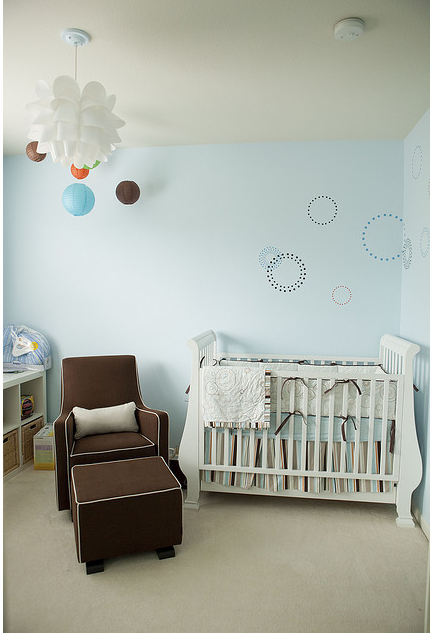 Modern boy nursery picture with white crib and chocolate nursery chair.PNG
