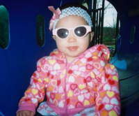 Cool looking baby girl with cute white sunglasses.PNG
