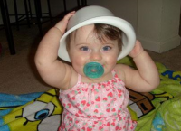 Creative baby girl using her plastic bowl as a cute white hat.PNG