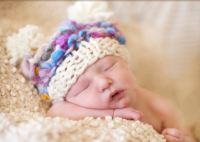 Sleepy newborn baby wearing a very cute baby hat.PNG