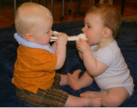 Sharing is a wonderful thing_two babies biting on Sophie the giraffe teether.PNG