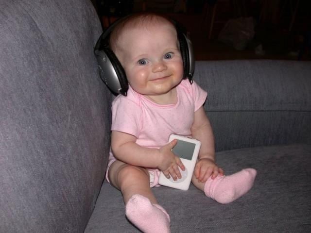 cute baby girl holding her ipod and weaing big headphones.jpg