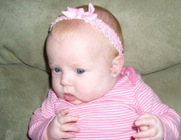 Image of baby girl in white and pink outfit and pink head band.PNG