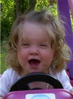 cute baby girl is ready to drive her toy car with great passion.jpg