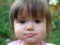 Cute big eyed baby toddler girl seems to be pouting.jpg