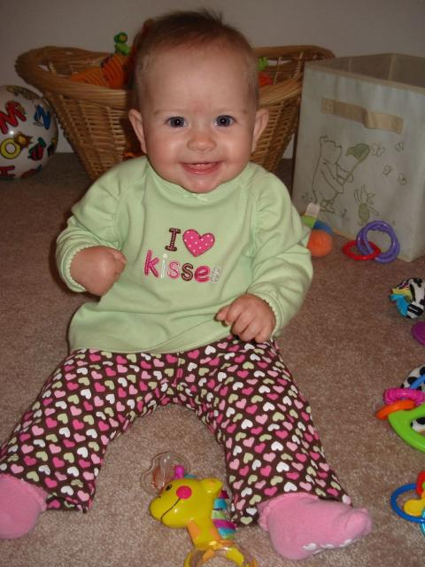 Smiling baby girl in a I Love Kisses top.jpg