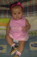 Baby girl in pink dress with bright pink head band.PNG