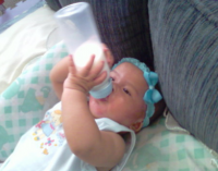 Baby girl drinking milk from bottle.PNG
