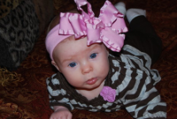 Baby girl with big head band looking so pretty.PNG