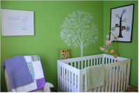Contemporary nursery with bright green wall painted with white tree wall art and classic white crib.PNG