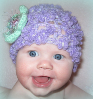 Pretty baby girl with her cute purple baby girl hat picture.PNG