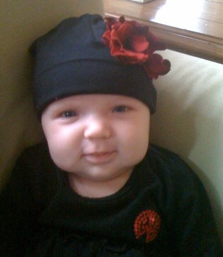 Adorable baby girl in her black baby hat with red flowers.PNG