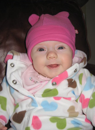 Happy baby girl with her cute pink hat photos.PNG