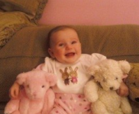 Happy baby girl smiling to the camera having teddy bears next to her.PNG