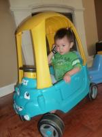 Darwin the 18 and a half month old toddler holds a phone while inside a play car.jpg