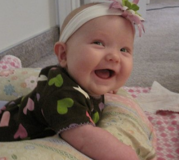 Happy baby girl wearing a cute baby headband.PNG