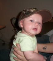 Baby wearing a brown hat looking to the camera with a cool look.PNG