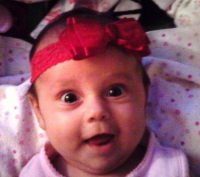 Baby girl with a pretty red bow headband.PNG