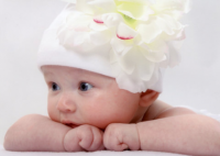 Baby photos shot ideas of a beautiful baby girl with wearing her white pretty floweral hat.PNG