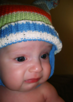 Cute baby boy wearing a colorful hat.PNG
