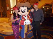 Darwin as a pirate held by daddy and mommy next to Mickey Mouse .jpg