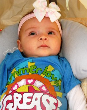 Cute serious looking baby girl with her pretty headband.PNG