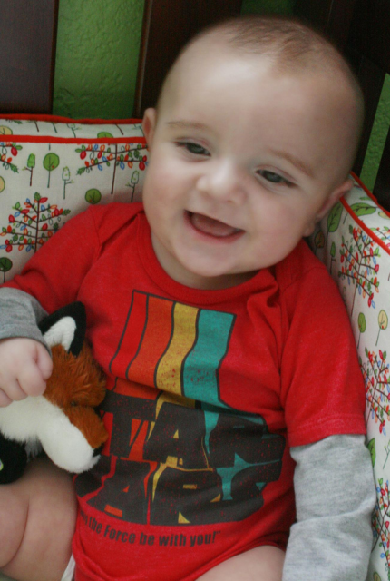 Cute baby smiling and holding teddy bear fox.PNG