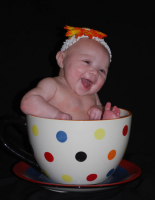 Happy baby picture of a baby girl sitting in a tea cup great baby photo shoot.PNG