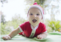 Baby in santa outfit smiling to the camera