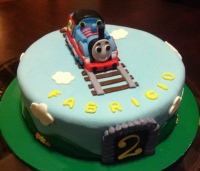 Large round birthday cake with Thomas the train with cute cake decoration with train tracks.PNG