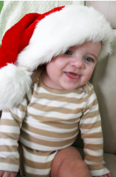baby smiling to the camera wearing a big xmas hat.PNG