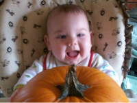 Baby smiling while receiving the pumpkin.PNG