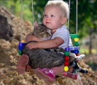 Kitten and baby sitting on a swing hugging each other.JPG