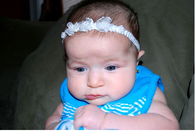 Cute baby girl in blue dress and with a white floral head band.PNG
