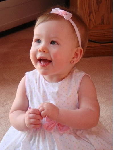 Baby girl in light pink dress with cute pink head band.PNG