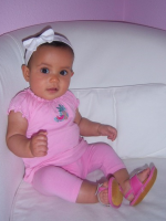 Baby girl in pink with white head band.PNG