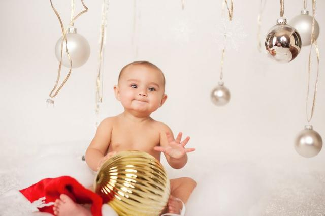 Baby Christmas photo shoot with baby holding a giant ornament.JPG