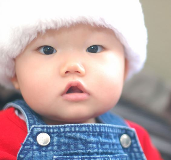 Close up picture of adorable chunky face with cute Santa hat.JPG