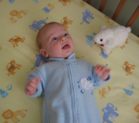 Baby boy in crib with a white lamb toy next to him.PNG