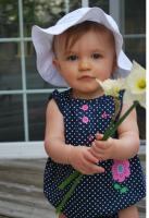 Adorable baby girl wearing a white hat holding flowers.PNG