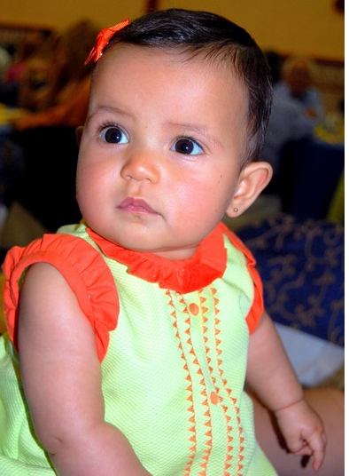 Beautiful baby girl in light green and orange dress with her matching head band.PNG