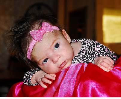 Image of baby girl with a pretty bright pink head band.PNG