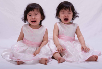 Crying twin toddler in pretty dresses.PNG