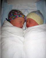 Picture of twins baby wearing hats and wrapped up in white towls.PNG