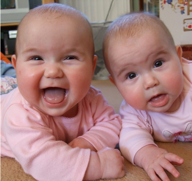 Very Cute Twin Baby Girls Smiling And Looking The Camera
