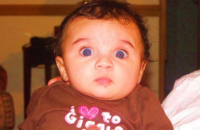 Cute funny baby girl with blue eyes looking straight to the camera.PNG