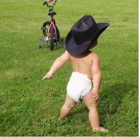 funny baby wearing a big black cowboy hat.PNG