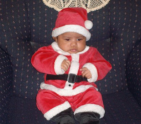 Black baby boy in santa outfit looking so cute.PNG