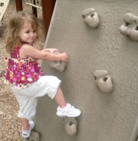 Pretty toddler girl climes on climing wall.PNG