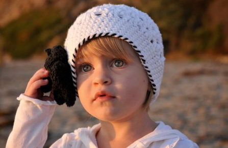 Pretty toddler girl wearing a cute white hat with black flower.PNG